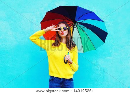 Fashion Pretty Cool Woman Holding Colorful Umbrella In Autumn Day Over Blue Background Wearing A Yel