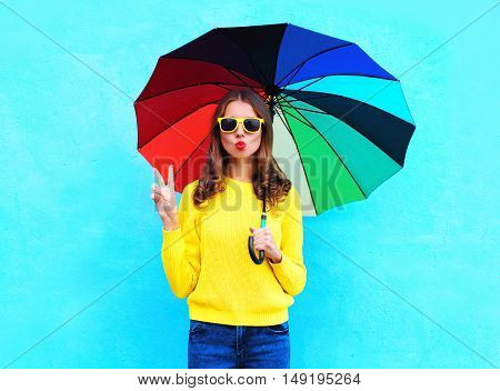 Fashion Pretty Cool Woman Holding Colorful Umbrella In Autumn Day Over Blue Background Wearing Yello