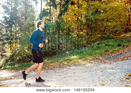 Young handsome runner with earphones in his ears, listening music, outside in sunny autumn nature