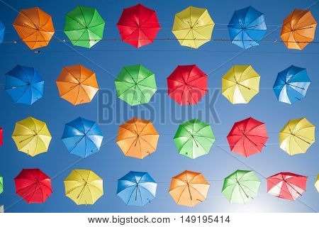 sky full of blue red green orange and yellow color umbrellas in row covering a public street in Torremolinos city Andalusia Spain Europe