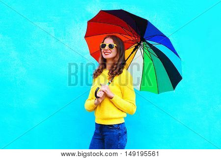 Happy Smiling Young Woman Holding Colorful Umbrella In Autumn Day Over Blue Background Wearing A Yel