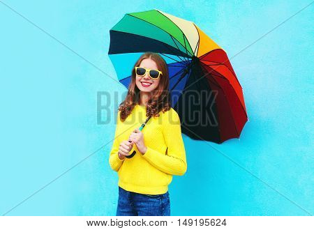 Happy Smiling Young Woman Holding Colorful Umbrella In Autumn Day Over Blue Background Wearing Yello
