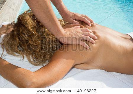 Portrait Of A Smiling Beautiful Woman Enjoying Shoulder Massage At Beauty Spa