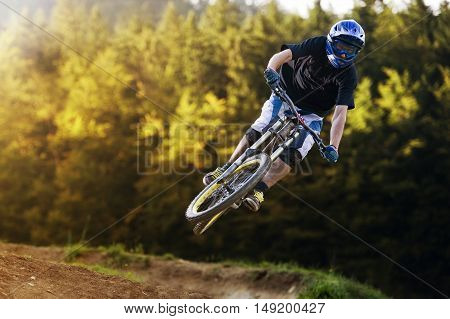Extreme mountainbiker rides and jump in autumn forest