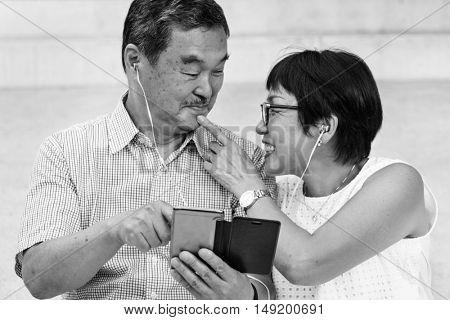 Senior Asian Couple Mobile Music Concept