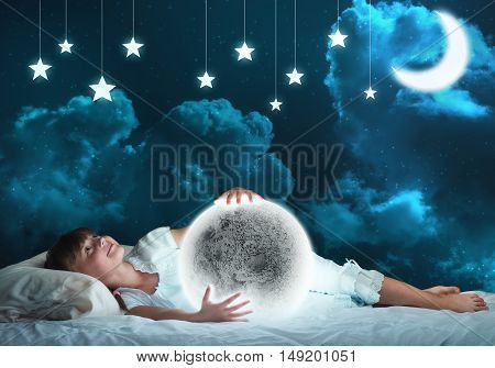 Cute girl in bed looking at glowing moon planet. Elements of this image are furnished by NASA.