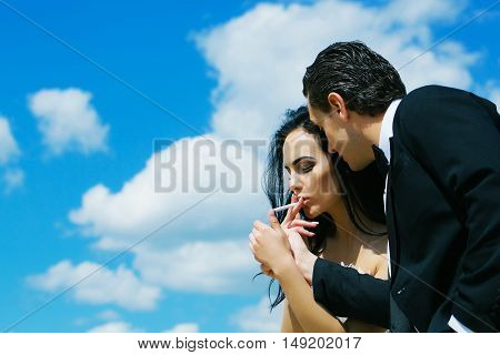Elegant man offers to woman beautiful brunette gas lighter to light cigarette for smoking on blue sky