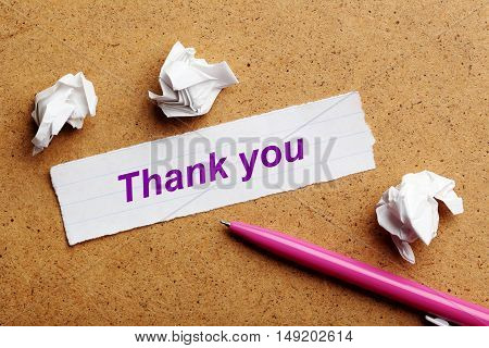 Sheet of paper on brown wooden background, thank you