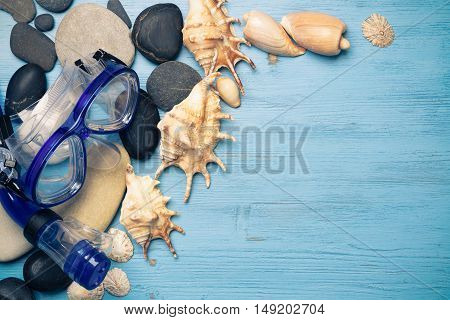 Diving mask with starfish and shells on blue wooden background.