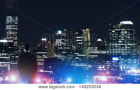 Elegant businessman looking at a night city skyline.