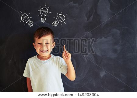Little cute boy is showing the concept of brainstorming using chalk drawings of light bulbs on the blackboard