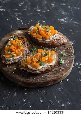 Pumpkin and goat's cheese bruschetta on a wooden cutting board on dark background. Healthy vegetarian snack