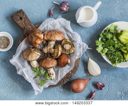 Mushrooms vegetables herbs spices and cream on a blue background top view. Cooking ingredients