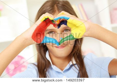 Beautiful little girl with painted hands, close up