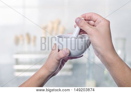 Scientist Using Pestle And Mortar In Laboratory
