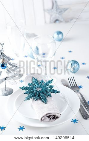 Christmas table setting in blue and silver colors with small tree and decorations.