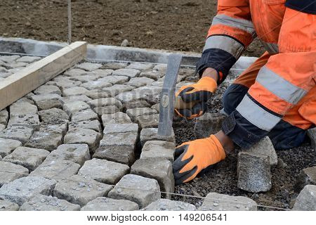Workers sets painstakingly and accurately cobblestone - closeup