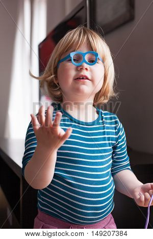Little Kid Playing With Toy Glasses