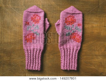 Hand knitted mittens on wooden background. Pink mittens with pattern from flowers