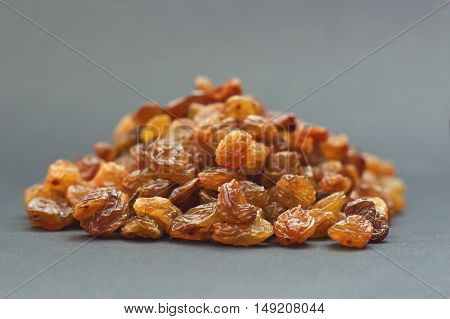 Pile of dried raisins on a gray background