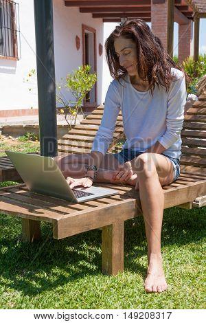 Woman Using Laptop At Garden