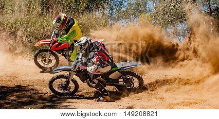 Two motocross riders race around a corner