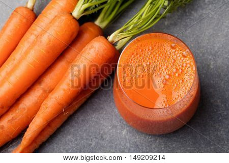 Carrot juice in glass and fresh carrots Healthy food on grey stone background Top view