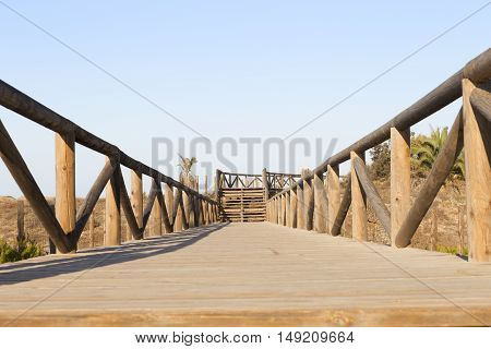 bridge footpath with wooden fences. Access to the beach