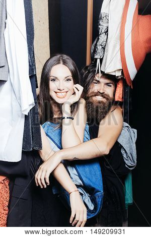 Fashion couple denuded of brunette girl and bearded man choose clothes to wear near rack in wardrobe closet