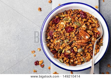 Healthy breakfast. Fresh granola, muesli with pumpkin, pecan nuts, cranberries and maple syrup in white bowl Copy space. Top view