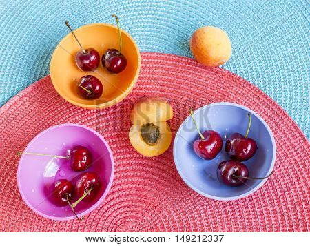 fresh and sweet cherries in colored bowls and apricot on pink an blue place mat. Summer fruit