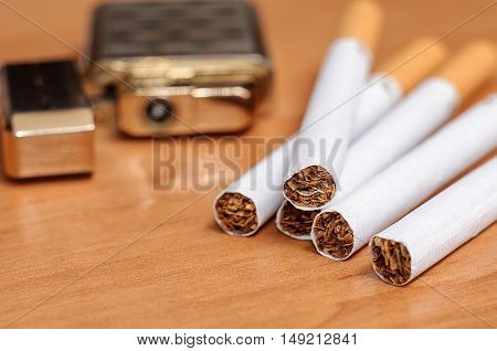 Cigarette and lighters placed on the wooden floor. Smoking concept and background
