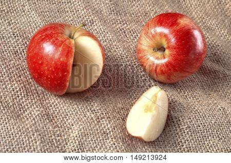 Fresh apple on burlap textile texture background.