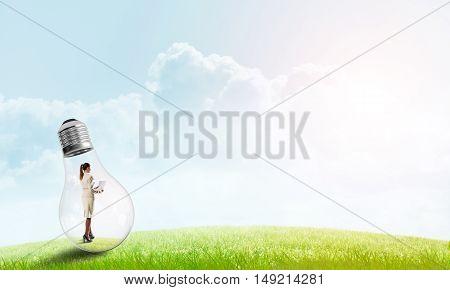 Businesswoman inside glass light bulb outdoors looking away