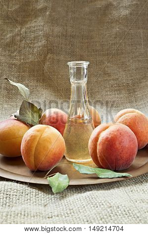 Fresh and tasty apricot fruit and apricot brandy on a plate.