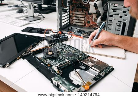 Computer motherboard diagnostics, close-up. Programmer inspecting circuit and note results on paper. Electronic repair, fix, renovation concept