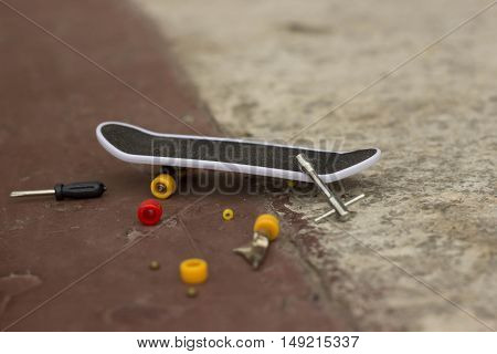 a very small skateboard with the wheels removed, next to the tools a screwdriver and a wrench, a smaller version, a sports Board for riding