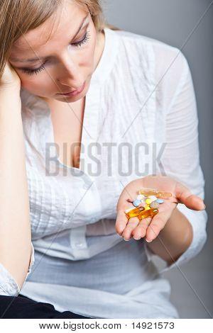 Woman holding pharmaceuticals on neutral bg