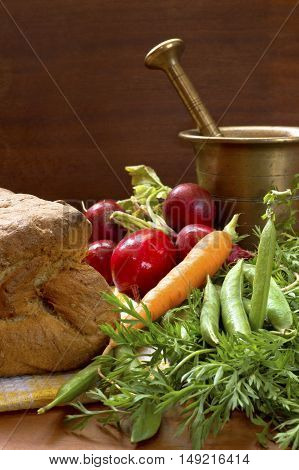 Tasty fresh vegetable and crunchy home made bread with old bronze mortar.