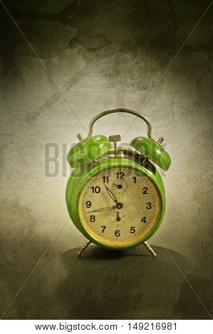 Green old style alarm clock over a grunge background