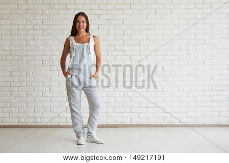 Smiling beautiful woman standing and holding hands in pockets, white brick wall on background
