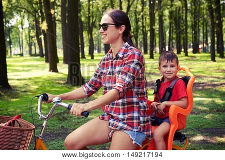 Mom and her small son prefer a healthy lifestyle. They are eager to start the day with a bicycle ride along the park. They are wearing casual outfits