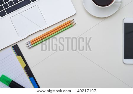 Top view of white office desk with phone, stationery and a cup of coffee on it