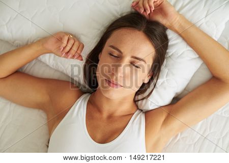 Top view of beautiful young woman holding hands behind head while lying on the bed and smiling