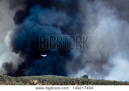 White Aircraft Flying Ahead of the Dense Black Smoke Rising from the Raging Wildfire