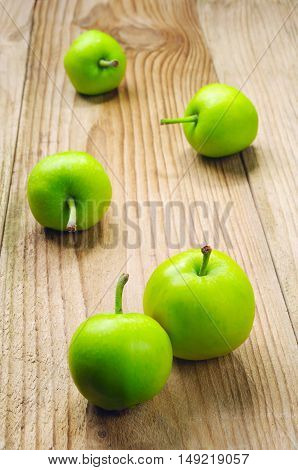 Green apples on a wooden table closeup
