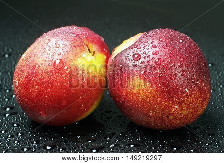Two fresh nectarines with water drops on black