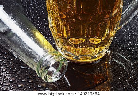 Glass of beer and an empty bottle with drops of water