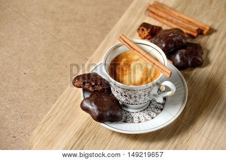 Cup Of Hot Coffee, Cinnamon Sticks, Cookies And Chocolate On Wooden Table