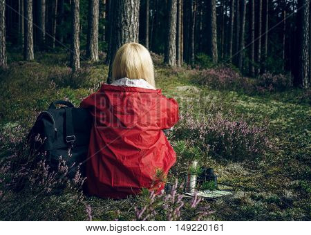 Young active woman tourist sitting in a clearing in the forest and looking at the forest. Healthy active lifestyle concept. Tourism